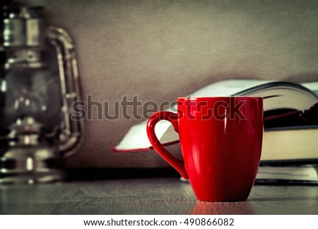 Red mug on wooden table  against grunge wall