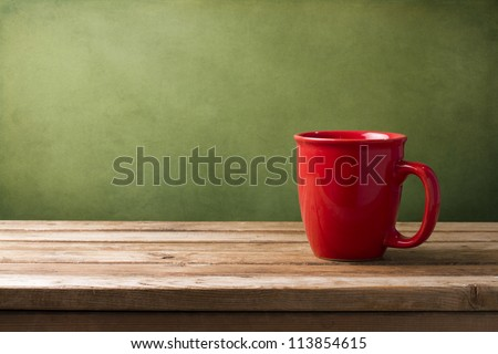 Red mug on wooden tabletop against grunge green wall