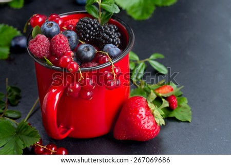 red mug with fresh ripe berries on black stone background, low key - stock photo