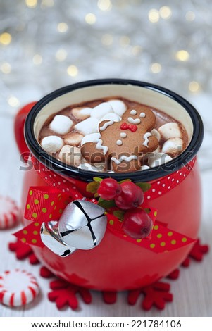 Red mugs with hot chocolate, marshmallows and gingerbread man