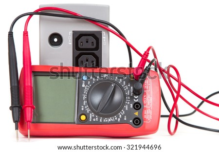 Red multimeter and UPS (uninterruptible power supply)Multimeter. Instrument for measuring voltageMeasurements in electrical instruments - stock photo