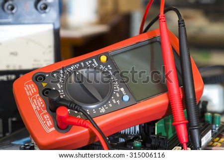 Red Multimeter. Instrument for measuring voltage.Measurements in electrical instruments - stock photo