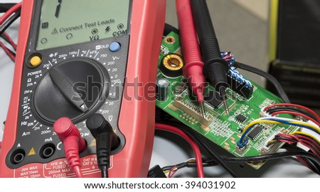 Red multimeter on printed-circuit boards - stock photo