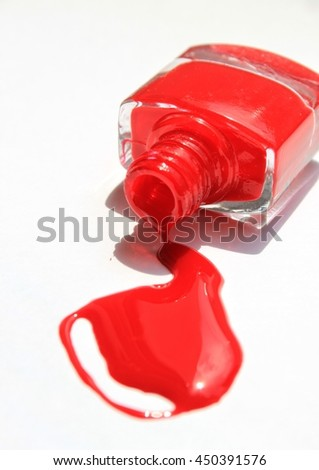 Red nail polish (enamel) drops with bottle on white background