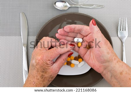 Red nailed elderly woman's hands picking pills and capsules from a plate on dinner table - stock photo