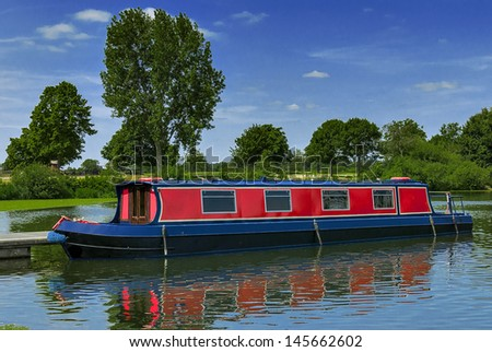 Red narrow boat at a mooring on a summers day in the countryside - stock photo