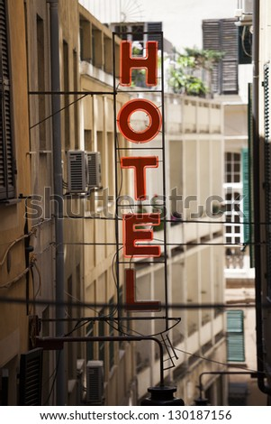 Red neon Hotel sign in old town - stock photo
