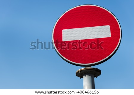 Red no entry traffic sign isolated on clear blue sky - stock photo