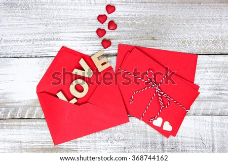 Red note cards tied in string by envelope with the word LOVE and hearts coming out on white rustic antique wooden background; Valentine's Day and love concept - stock photo
