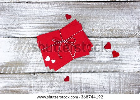 Red note cards tied in string  with scattered hearts on white rustic antique wood background; Valentine's Day and love concept - stock photo
