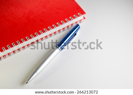 Red Notebook And Blue Pen - stock photo