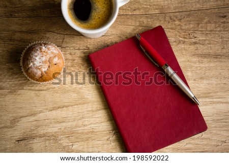 Red notebook with pen on wooden table, top view - stock photo