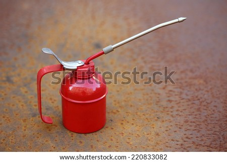 Red oiler close up over rusty grunge background - stock photo