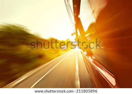Red old bus going fast on the highway with motion blur background
