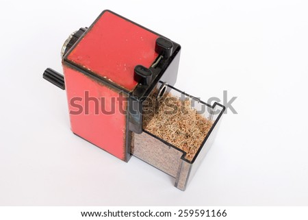 Red old mechanical sharpener : Focus on colorful pencil shavings  - stock photo