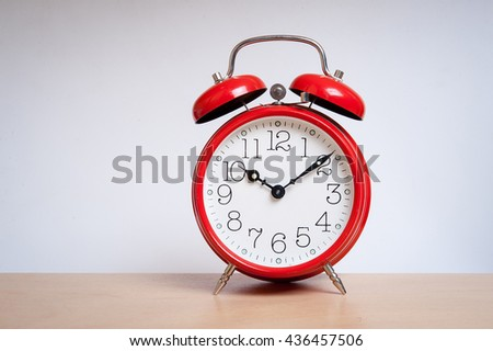 red old retro style alarm clock on wood table. Alarm clock shows ten minutes after ten o`clock - stock photo
