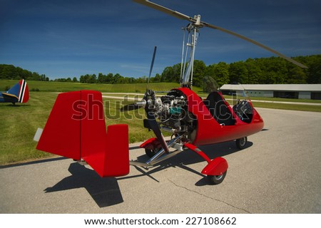 Red open-cockpit autogyro parked at the airfield - stock photo