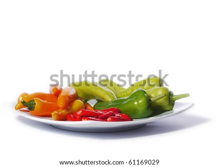 Red, orange and green chili peppers from Thailand on a white plate. Isolated on white.