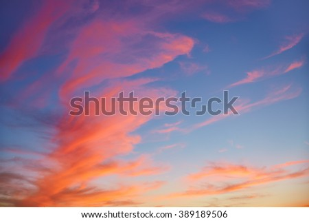 Red orange clouds at sunset over blue sky - stock photo