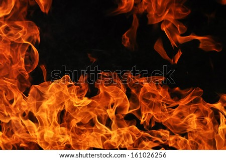 Red-orange fire flames on a dark background - stock photo