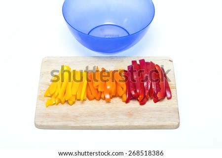 Red orange yellow peppers sliced on a cutting board with blue bowl - stock photo