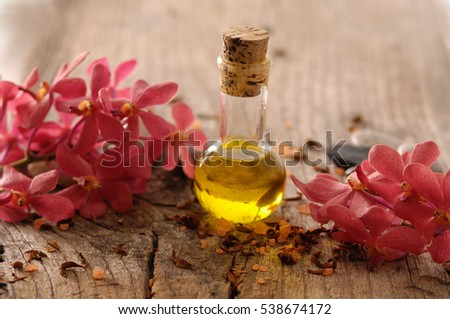red orchid with massage oil ,stone on old wood