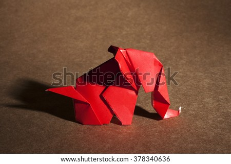 Red origami elephant isolated on craft paper background. - stock photo