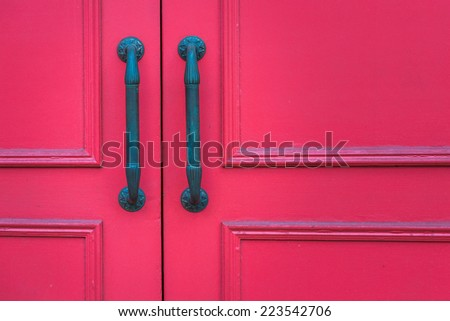 Red ornate door with two long handles - stock photo