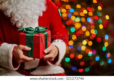 Red package bound by silk green ribbon held by Santa Claus - stock photo