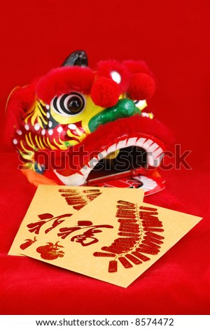 Red packets and chinese lion head decoration over red background - stock photo