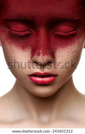 Red paint on face of fashion beauty model - stock photo