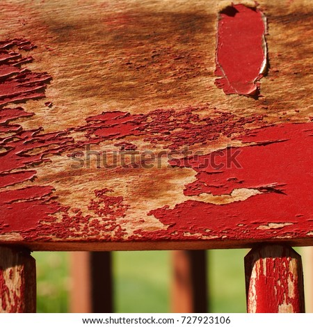 Red paint peeling off of an old country style wooden chair.