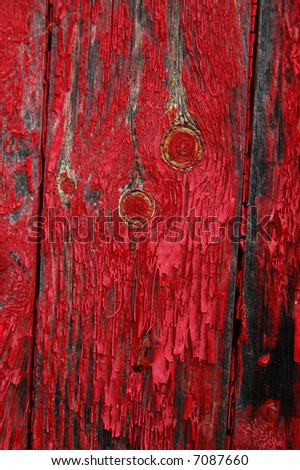 Red paint peeling on knotted wood boards - stock photo