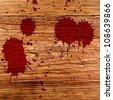 red paint splash on wood background - stock photo