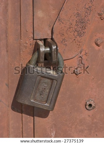 Red painted steel garage gate locked with padlock - stock photo