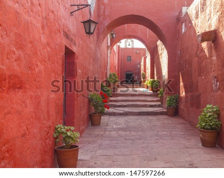 Red painted walls and arches design of alleyway through the Santa Catalina Monastery in Arequipa, Peru. - stock photo