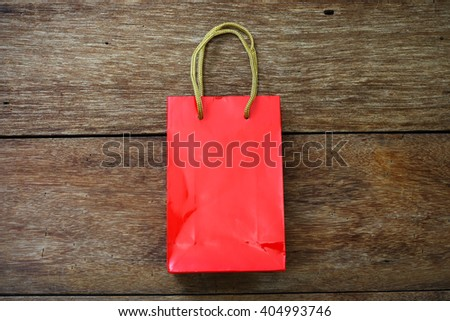Red Paper bag on a wooden texture background - stock photo