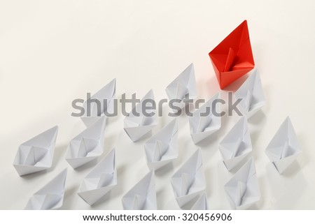 red paper boat leading white ones, leadership concept - stock photo