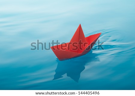 red paper boat sailing on water causing waves and ripples - stock photo