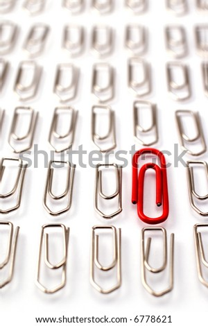 Red paper clip among rows of metal paper clips - stock photo