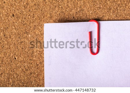 Red paper clip attached to multiple sheets of paper