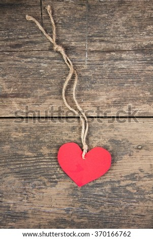 Red paper heart connected with a rope on a wooden background - stock photo