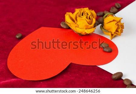 Red paper heart lying on the envelope with two dried yellow roses and coffee beans - stock photo