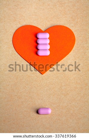 Red paper heart shape on brown paper with row of small pink pill on and copy space on the bottom. Heart health concept.  - stock photo