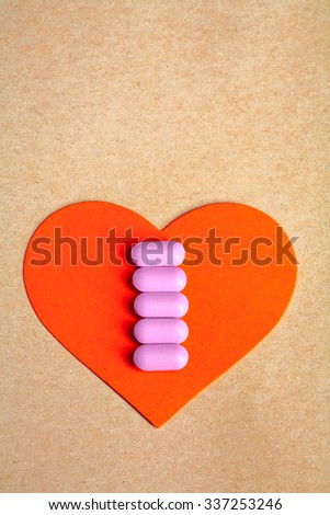 Red paper heart shape over craft paper with row of small pink pill on and copy space on the top. Heart health concept.  - stock photo