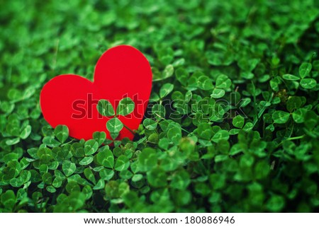 Red paper hearts in green clover. Saint Patrick's day conceptual image, celebrate spring season. - stock photo