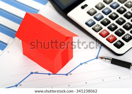 red paper house and calculator on graphs, real estate concept - stock photo