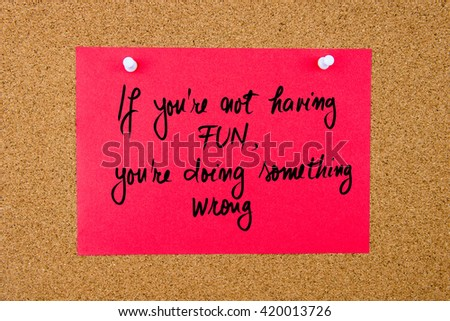 Red paper note with handwritten text If You Are Not Having Fun, You Are Doing Something Wrong pinned on cork board with white thumbtacks - stock photo