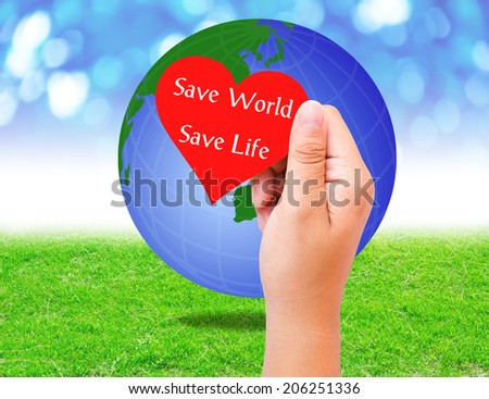 Red paper shape in hand and globe on grass background. environment concept. Save world Save life - stock photo