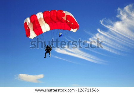 Red parachute landing on windy day..